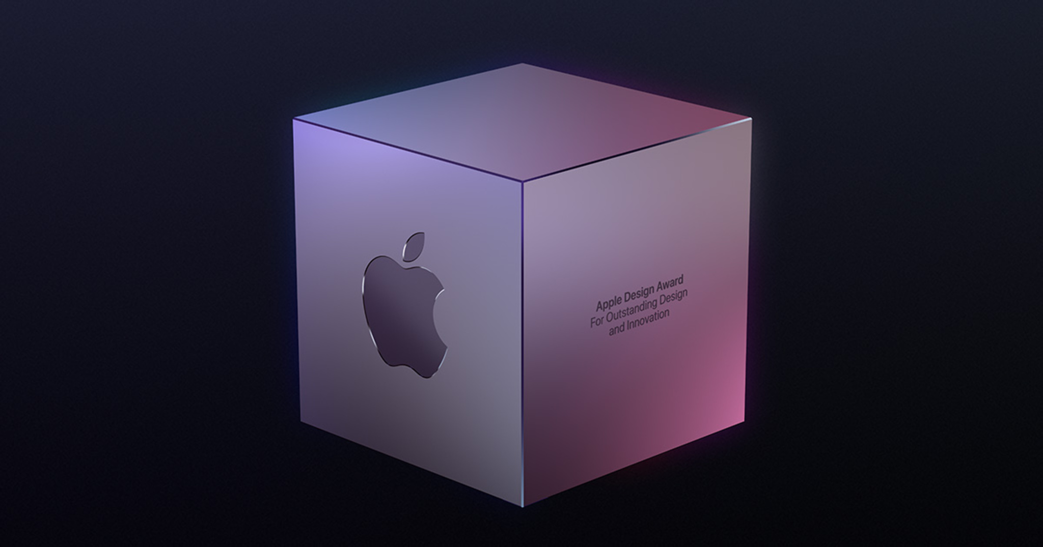 """A silver-colored metallic cube sits on a black background. It's engraved on the left side with the Apple logo and on the right side with the words """"Apple Design Award For Outstanding Design and Innovation""""."""