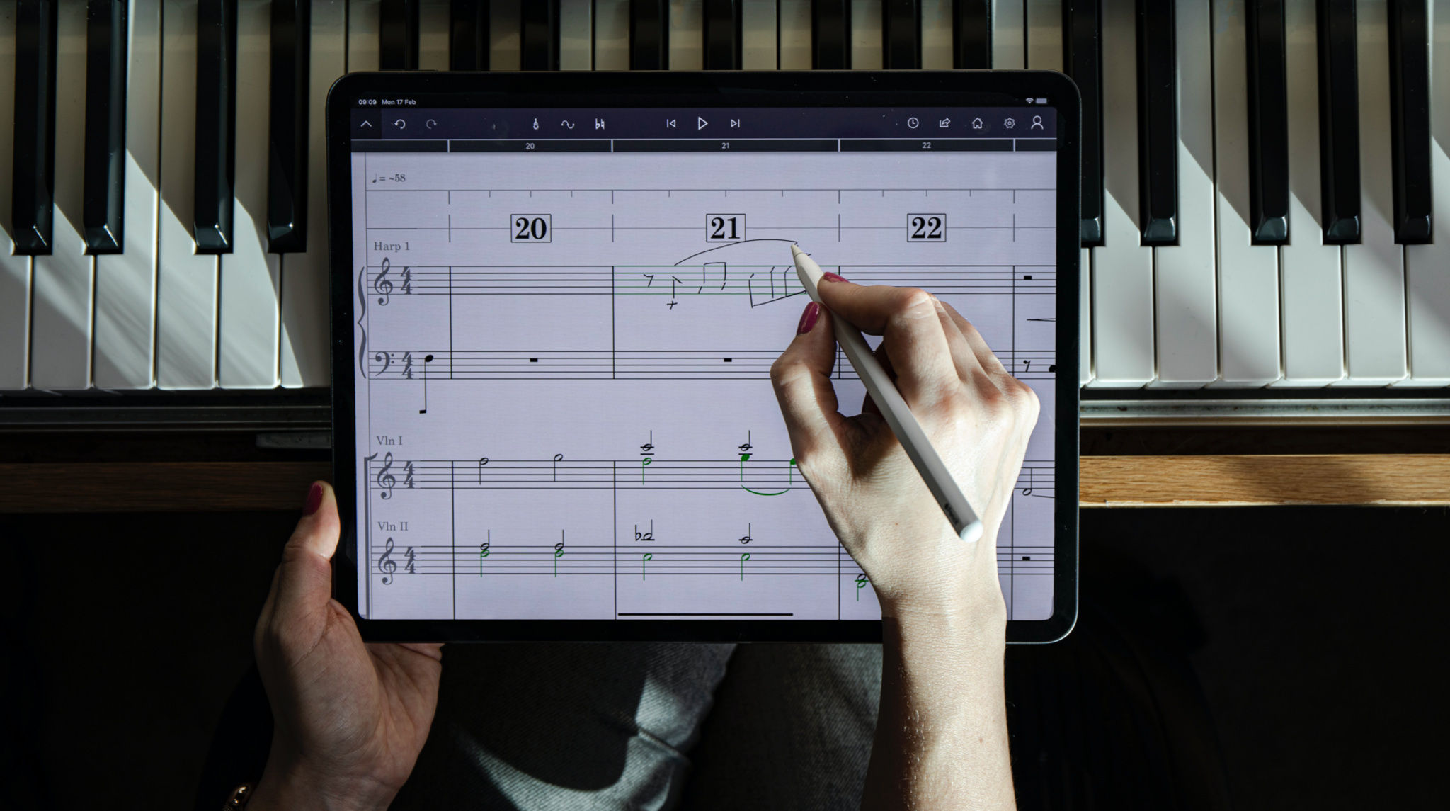Person using Apple Pencil to add notes to StaffPad on iPad Pro in front of piano